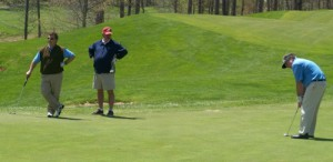 Manny Molina and a friend watch David Ede prepare to make the perfect putt on the opening day of the 2013 Spring Break Meeting on April 26 at Stonewall Resort.