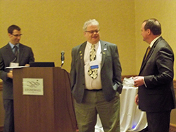 WVOS President Brett Whitfield looks on as AAOS Councilor Greg Krivchenia presents AAOS President David Teuscher with a true West Virginia gift that will become a diamond by the end of his term.